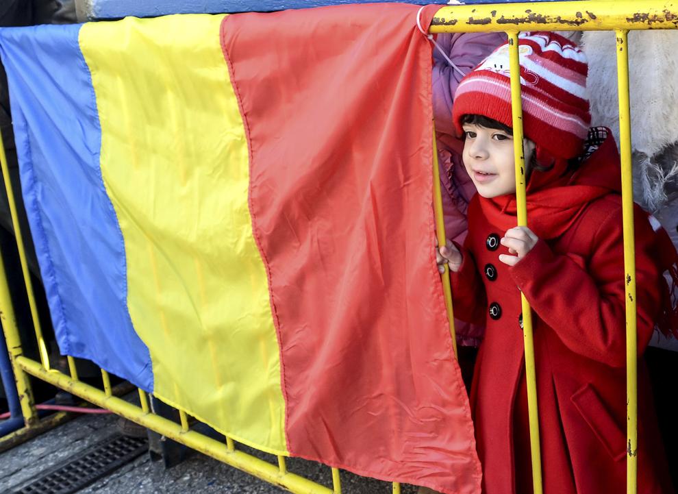 Un copil urmăreşte, din spatele unui gard pe care este prins un drapel naţional, parada militară, organizată cu ocazia Zilei Naţionale a României, în Piaţa Unirii din Iaşi, duminică, 1 decembrie 2013.