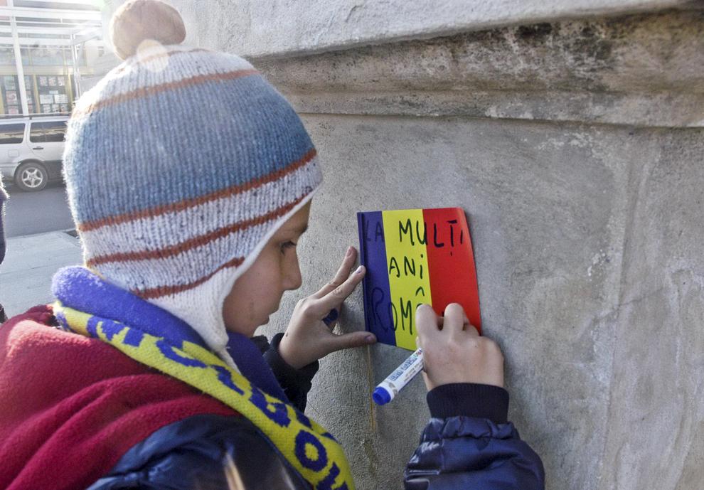 """Un copil scrie """"LA MULŢI ANI, ROMÂNIA!"""" pe un steag tricolor, în timpul desfăşurării ceremoniilor prilejuite de Ziua Naţională a României, în Piaţa Tricolorului din Bacău, duminică, 1 decembrie 2013."""