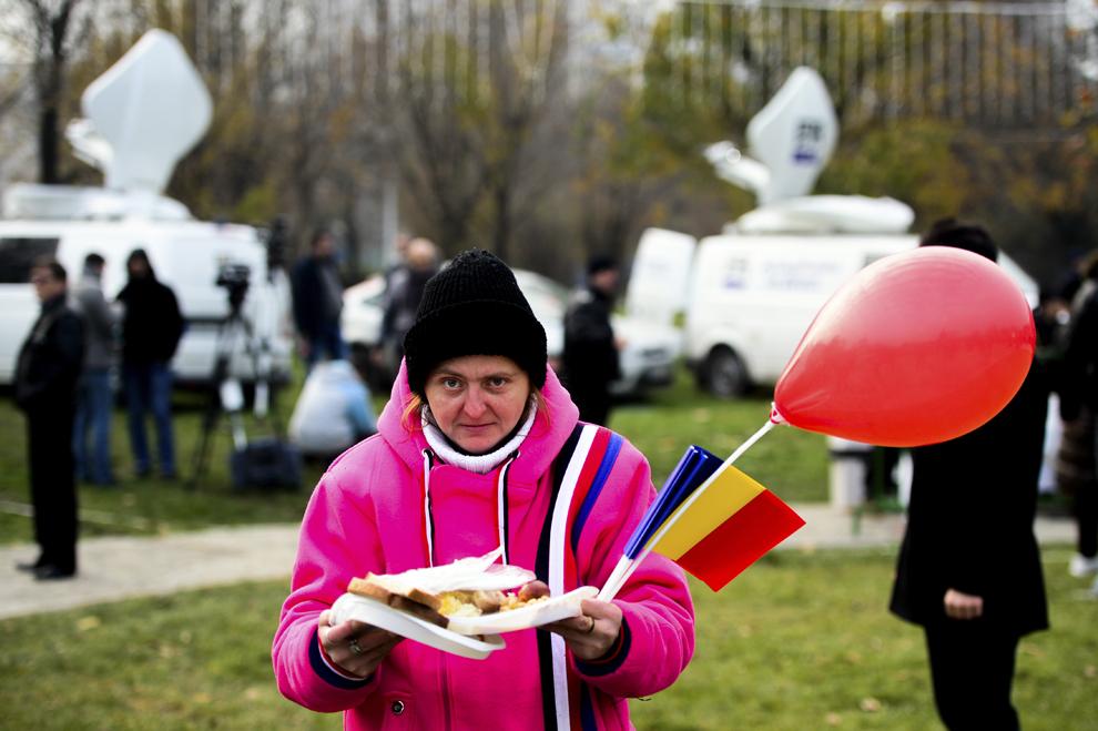 O femeie ţine în mâini porţii de fasole cu cârnaţi, oferite de Primăria Sectorului 3 cu ocazia Zilei Naţionale a României, în parcul Alexandru Ioan Cuza din Bucureşti, duminică, 1 decembrie 2013.