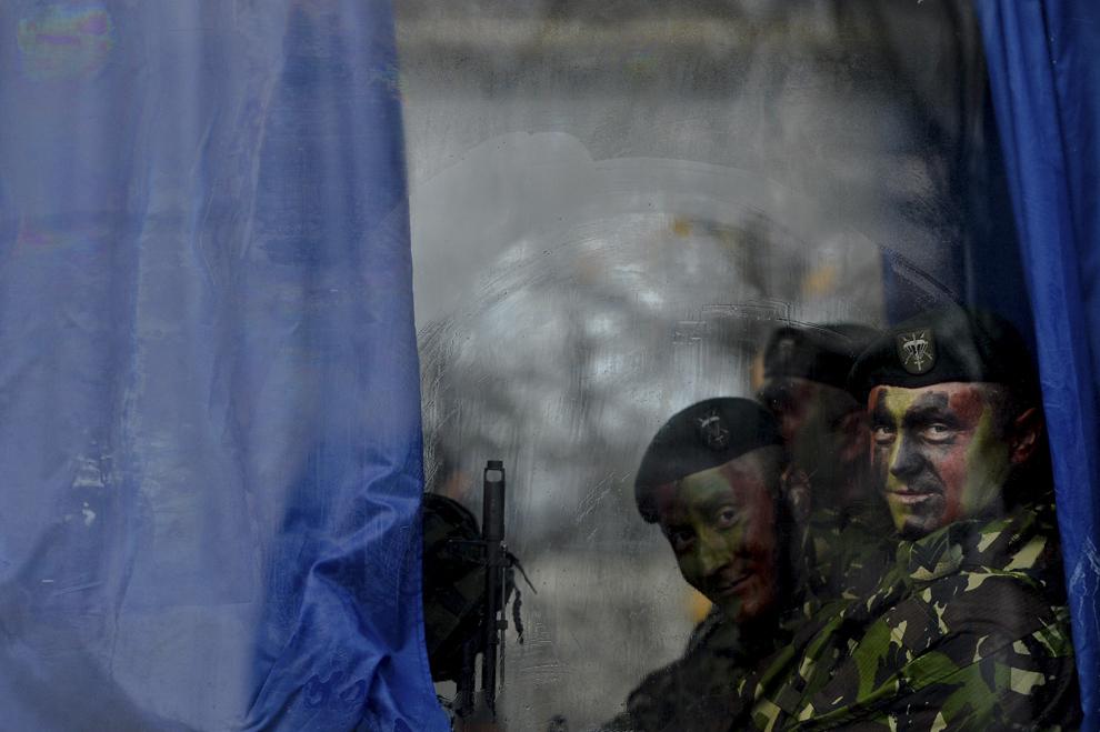Militari privesc către aparatul de fotografiat, înaintea paradei organizate cu ocazia Zilei Naţionale a României, în Piaţa Arcului de Triumf din Bucureşti, duminică, 1 decembrie 2013.
