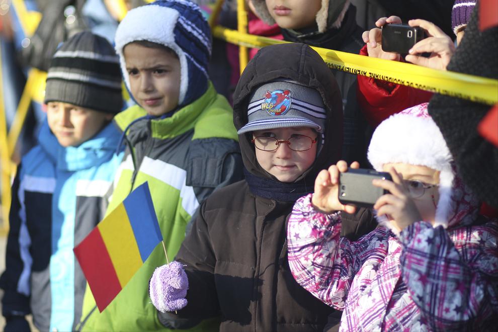 Copii privesc militarii care defilează prin faţa Consiliului Judeţean Timiş, cu ocazia Zilei Naţionale a României, în Timişoara,  duminică, 1 decembrie 2013.