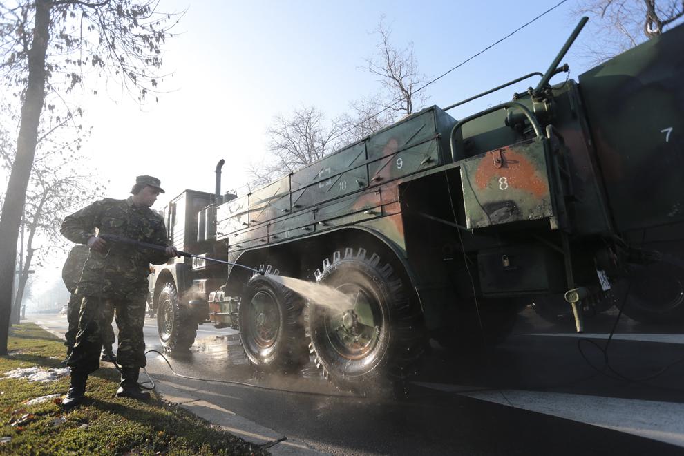 Un militar spală roţile unui autovehicul, înaintea paradei militare, organizate cu ocazia Zilei Naţionale a României, în Bucureşti, duminică, 1 decembrie 2013.