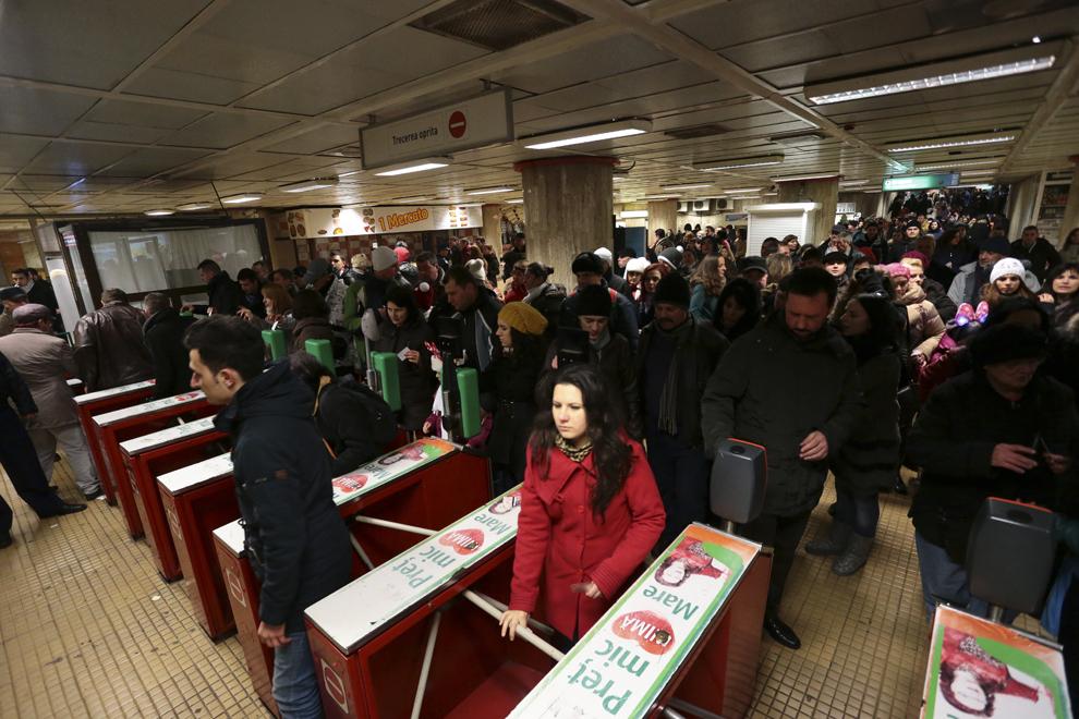Zeci de persoane aşteaptă la rând pentru a intra în staţia de metrou Unirii 1, după ce au participat la spectacolul de artificii din Piaţa Constituţiei, cu ocazia Revelionului, în Bucureşti, miercuri, 1 ianuarie 2014.