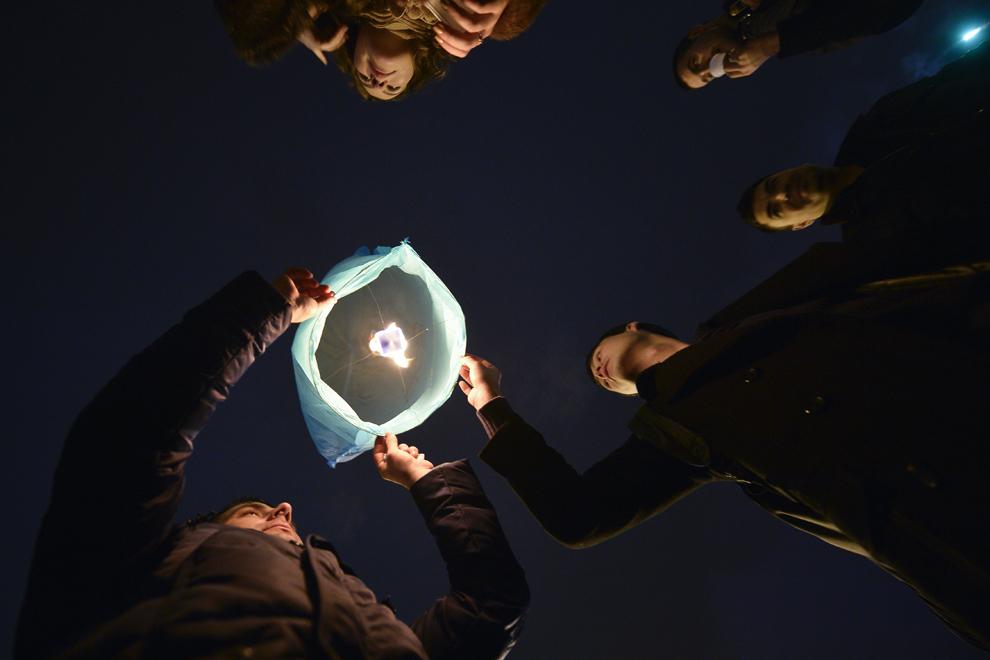 Tineri lansează lampioane, în Piaţa Revoluţiei din Bucureşti, miercuri, 1 ianuarie 2014.