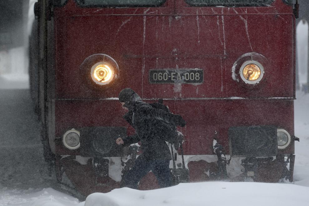 Un tânăr traversează calea ferată prin dreptul unui tren, în Gara de Nord, în Bucureşti, miercuri, 29 ianuarie 2014.