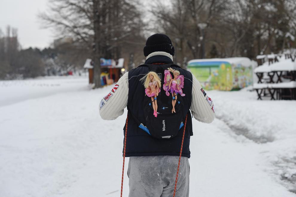 Un bărbat îşi trage fetiţa pe sanie pe o alee din parcul Alexandru Ioan Cuza, duminică, 2 februarie 2014.