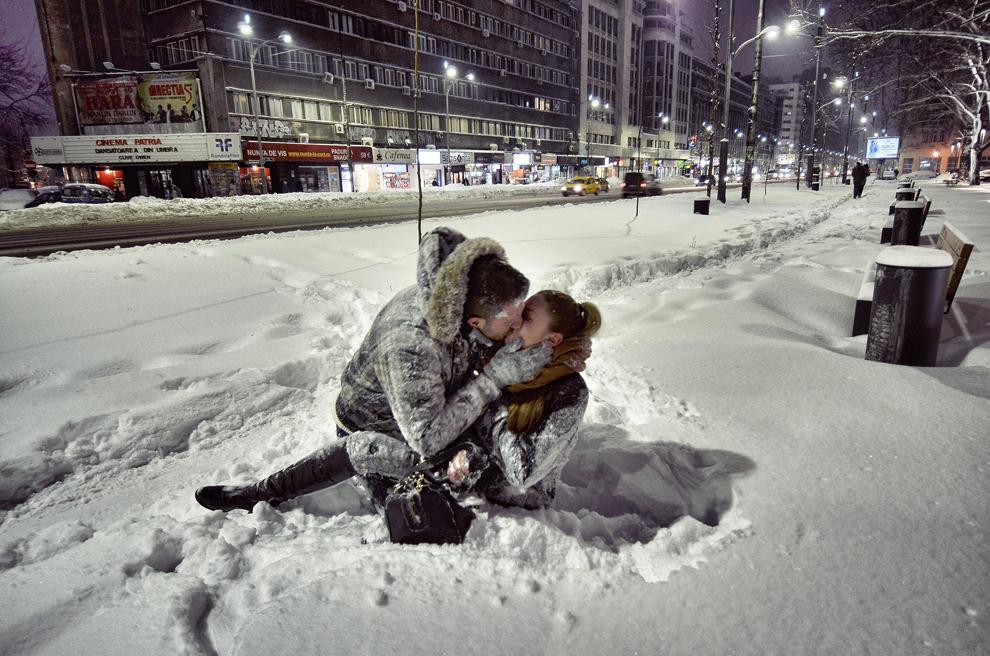 Doi tineri se sărută în zăpadă, pe bulevardul Magheru din Bucureşti, luni, 27 ianuarie 2014.