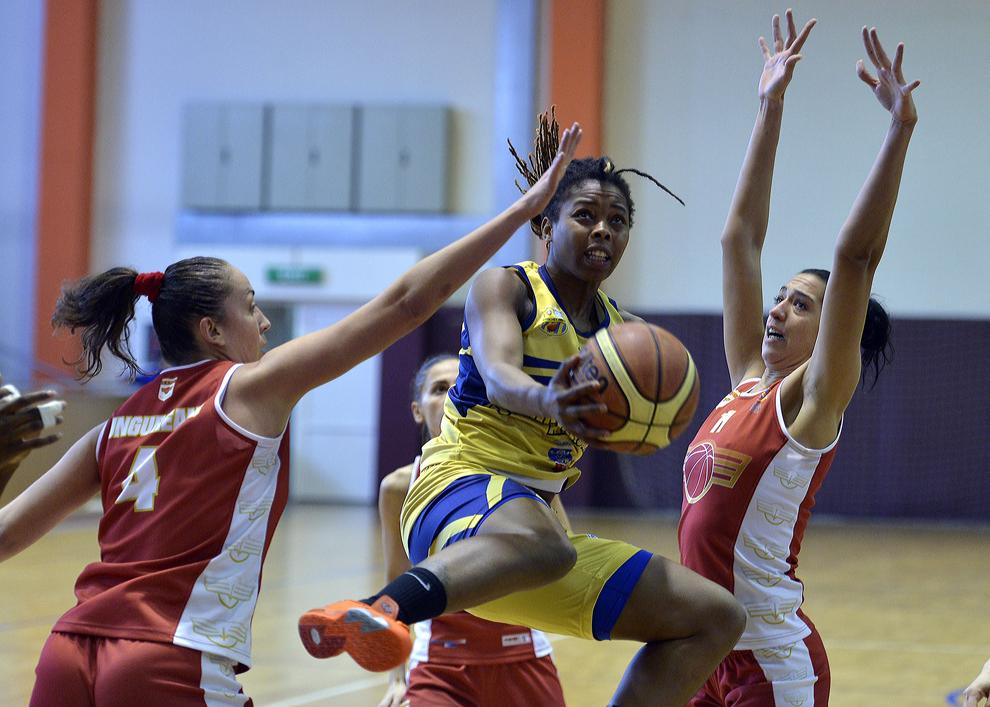 Donica Ayana Cosby (C), de la U Goldis ICIM Arad, încearcă să puncteze de lângă Roxana Bejan (D), de la CS Rapid Bucureşti, în meciul de baschet disputat în Bucureşti, luni, 3 februarie 2014.