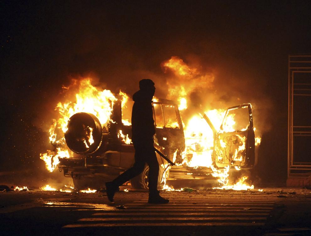 Un protestatar trece pe lângă un vehicul incendiat în oraşul Lviv, din vestul Ucrainei, marţi, 18 februarie 2013.