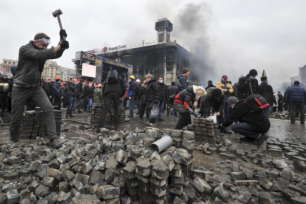 Protestatari sparg caldarâmul pentru a putea folosi pavajul drept muniţie împotriva forţelor de ordine, în Kiev, miercuri, 19 februarie 2014.