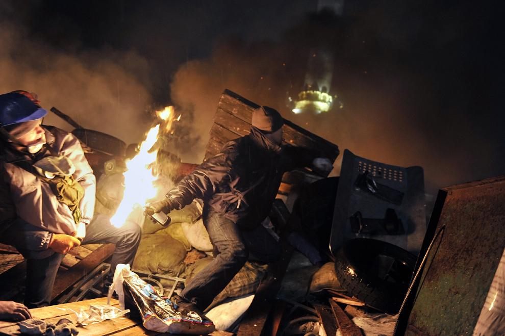 Un protestatar aruncă un cocktail Molotov către forţele de ordine, din sparele baricadei ridicate în piaţa Independenţei din Kiev, miercuri, 19 februarie 2014.