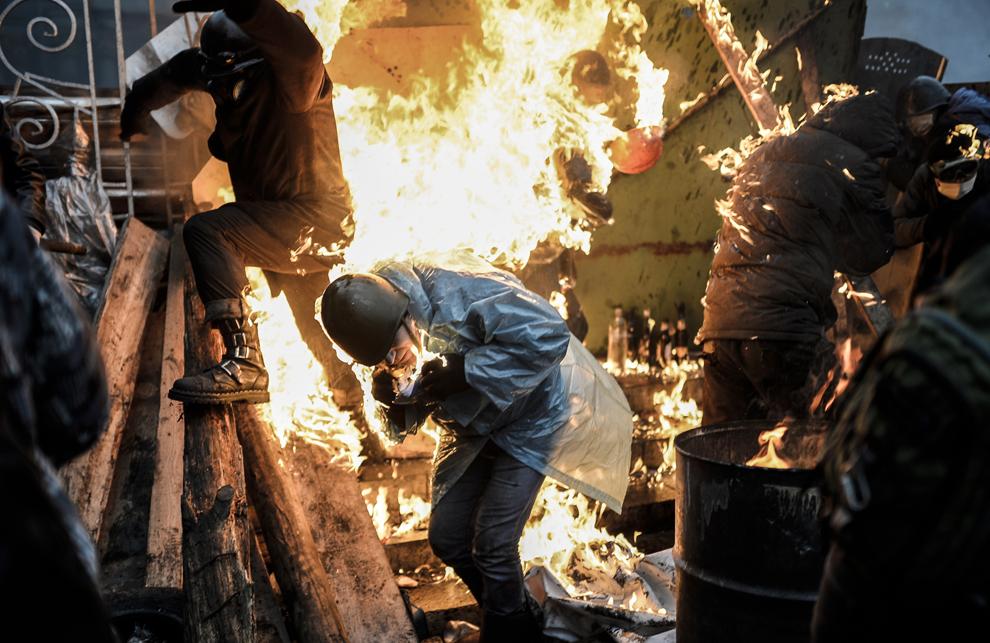 Mai mulţi protestatari sunt cuprinşi de flăcări în timpul încleştărilor dintre forţele anti-guvernamentale şi forţele de ordine, în Kiev, joi, 20 februarie 2014.