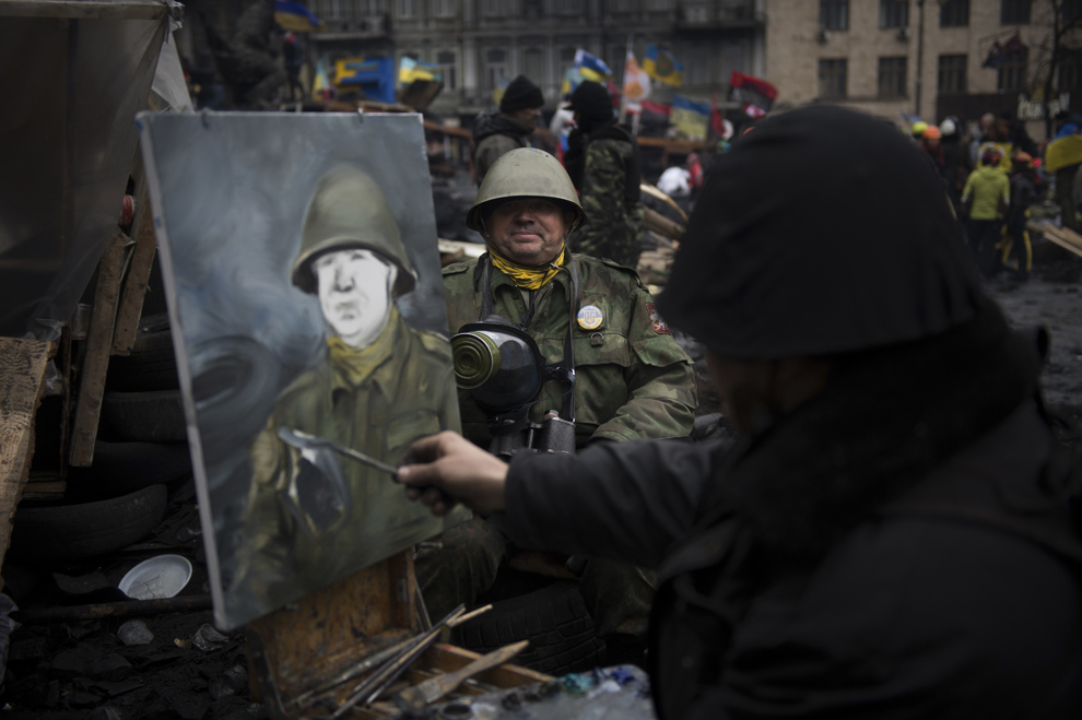Un pictor realizează un portret al unui protestatar anti-guvernamental îmbrăcat în uniformă militară, în Kiev, duminică, 16 februarie 2014.