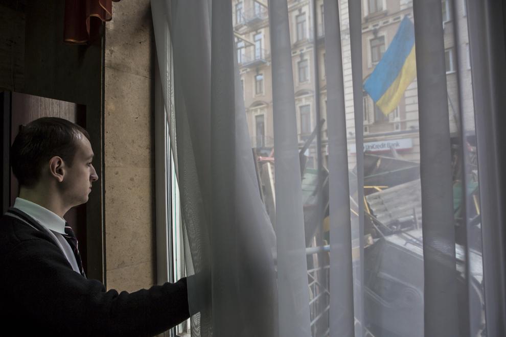 Un angajat al unui hotel din Kiev priveşte la construcţia unei baricade improvizate, pe o stradă adiacentă pieţei Independenţei, miercuri, 19 februarie 2014.