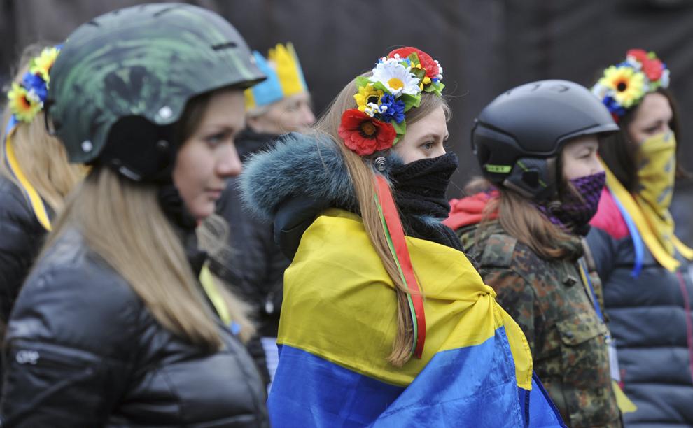 Activiste ale mişcării anti-guvernamentale Maidan privesc înlăturarea unei baricade pe strada Grushevsky, în Kiev, duminică, 16 februarie 2014.
