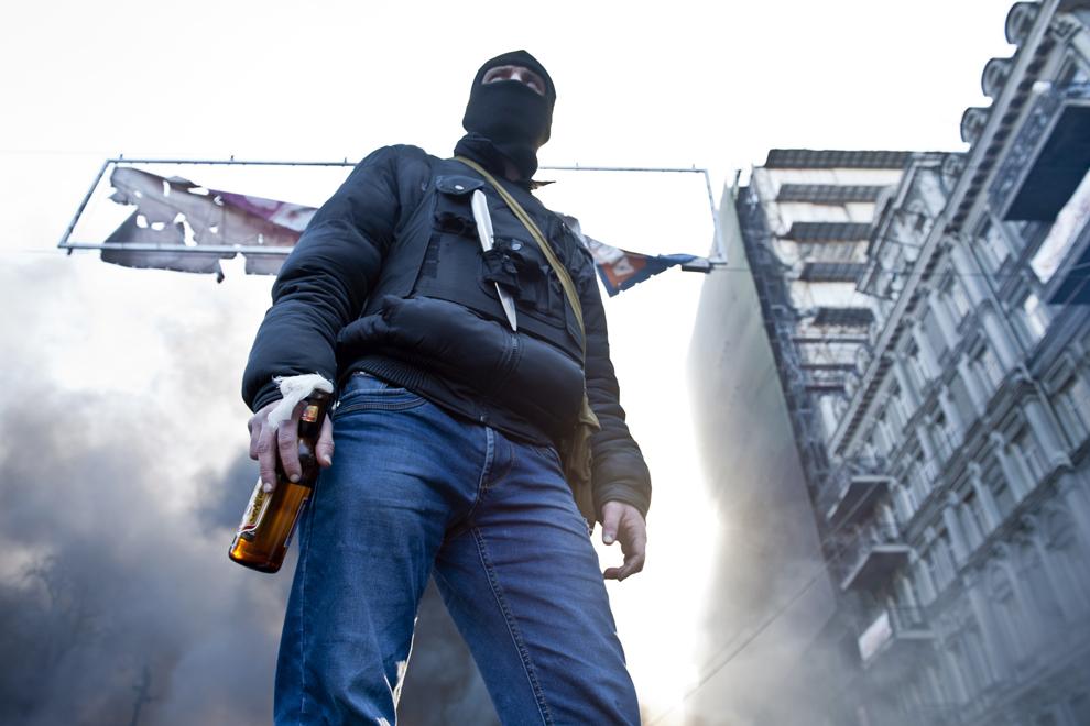 Un protestatar ţine în mână un cocktail Molotov în timpul ciocnirilor cu forţele guvernamentale, în Kiev, marţi, 18 februarie 2014.