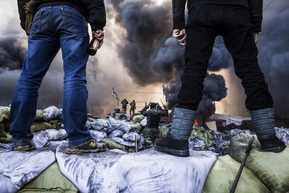 Protestatari privesc de pe o baricadă ciocnirile cu forţele de ordine, în Kiev, marţi, 18 februarie 2014.