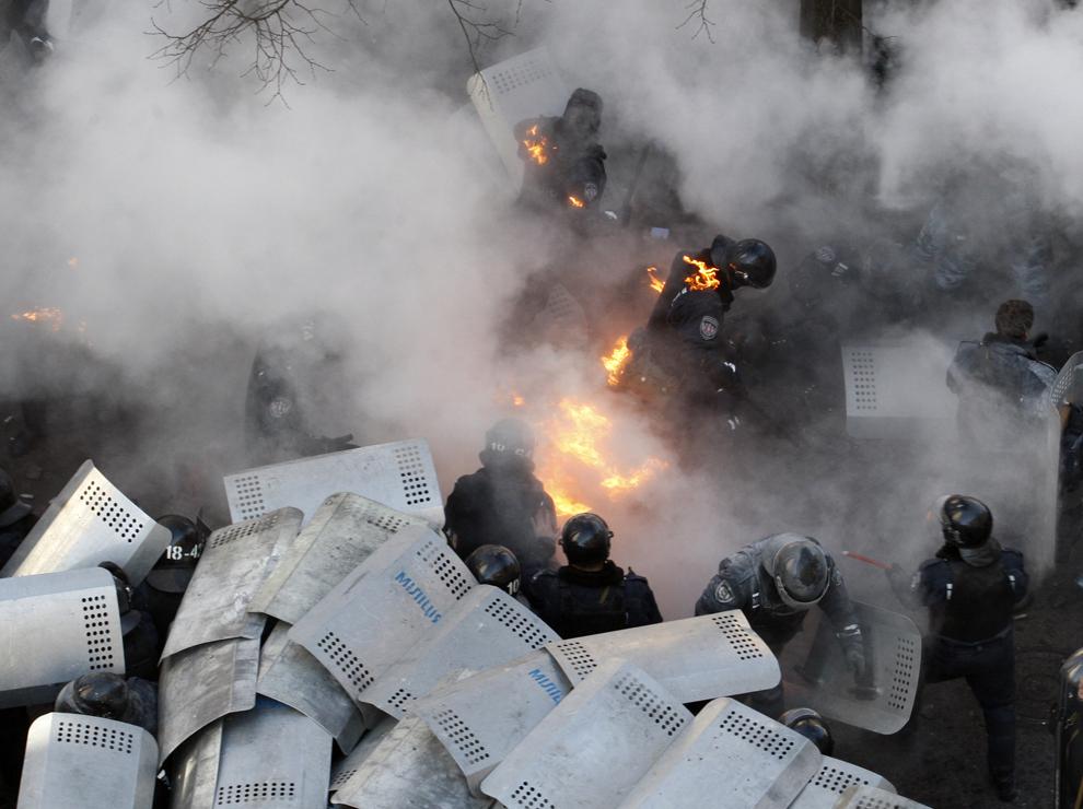 Membri ai forţelor de ordine încearcă să scape de flăcări, în timpul ciocnirilor cu forţele anti-guvernamentale, în Kiev, 18 februarie 2014.