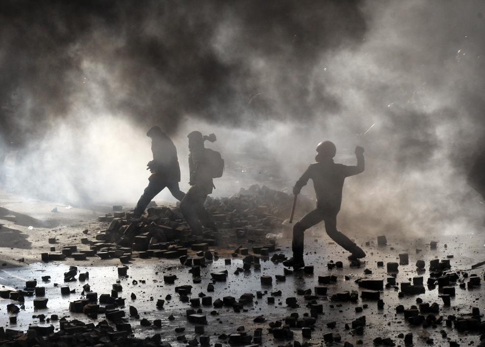 Protestatari anti-guvernamentali aruncă cu bucăţi din pavaj în forţele de ordine, în Kiev, marţi, 18 februarie 2014.
