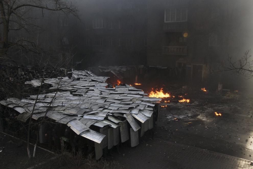 Membri ai forţelor de ordine se apără în timpul unei confruntări cu protestatari anti-guvernamentali, în Kiev, marţi, 18 februarie 2014.