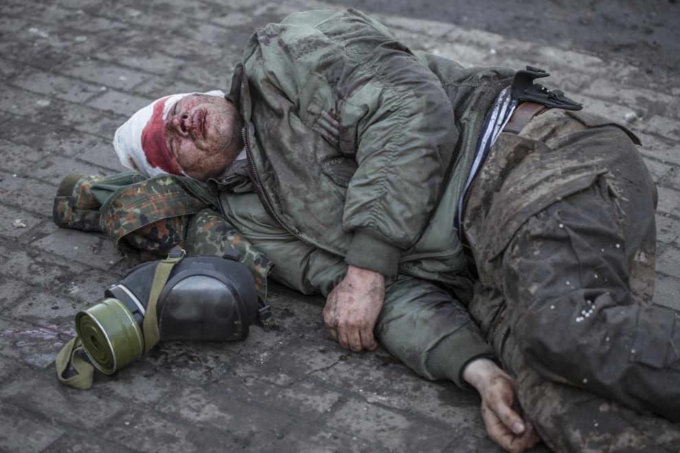 Un protestatar rănit se odihneşte pe pământ la finalul confruntărilor cu forţele de ordine, în Kiev, Ucraina, marţi, 18 februarie 2014.