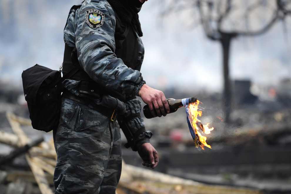 Un membru al forţelor speciale Berkut ţine în mână un cocktail Molotov înainte de a-l arunca, în Kiev, Ucraina, miercuri, 19 februarie 2014.