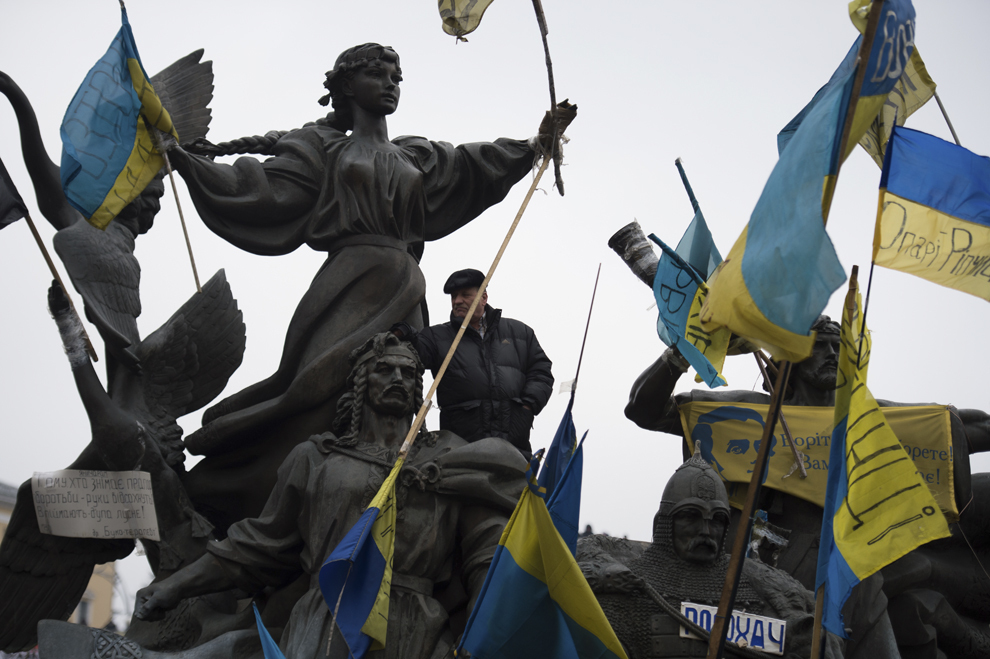 Un bărbat poate fi văzut lângă grupul statuar din centrul Pieţei Independenţei din Kiev, în timpul protestelor anti-guvernamentale din centrul Kiev-ului, duminică, 16 februarie 2014.
