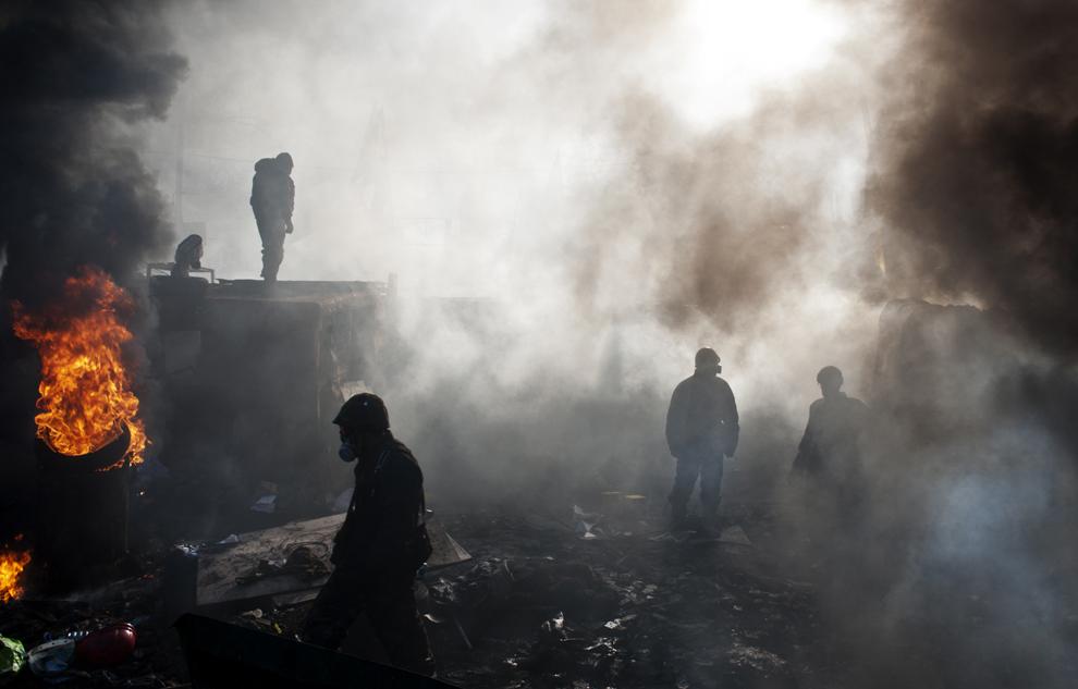 Protestatari anti-guvernamentali pot fi văzuţi prin perdeaua de fum ce se ridică din cauciurile arse în piaţa Independenţei din Kiev, marţi, 18 februarie, 2014.