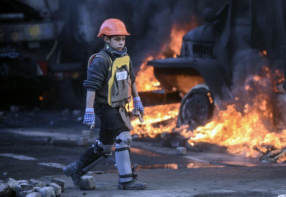 Un copil care poartă echipament de apărare improvizat participă la protestele anti-guvernamentale din Kiev, marţi, 18 februarie 2014.
