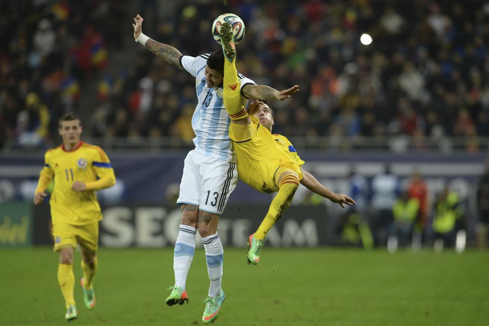 Marcos Rojo (S), de la selecţionata Argentinei, se luptă pentru balon cu Alexandru Măţel (D), de la naţionala României, în timpul meciului amical disputat pe Arena Naţională din Bucureşti, miercuri, 5 martie 2014.