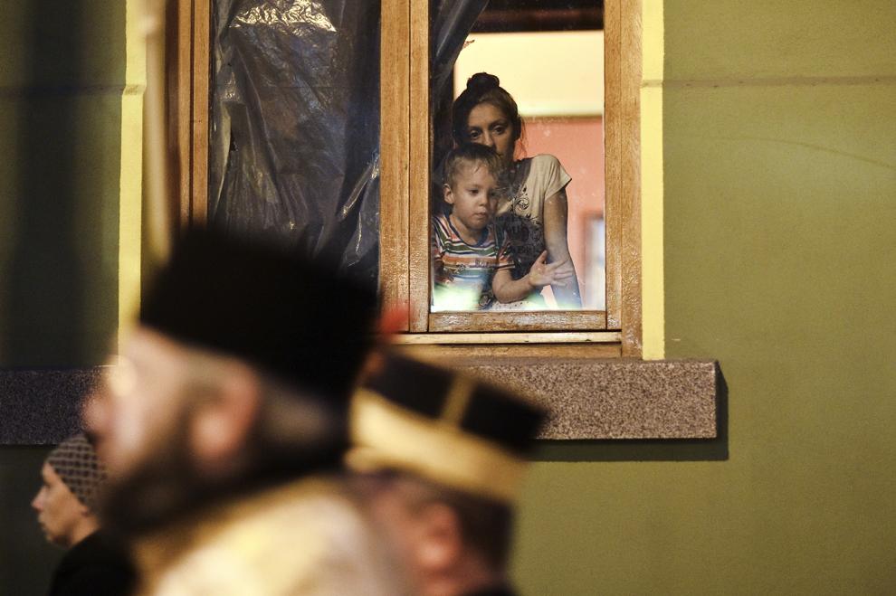 """Un copil şi mama sa urmăresc, de la geam, procesiunea religioasă prilejuită de sărbătorirea Duminicii Ortodoxiei, desfăşurată sub genericul """"Icoana – Fereastră spre Dumnezeu"""", în Bucureşti, sâmbătă, 8 martie 2014."""