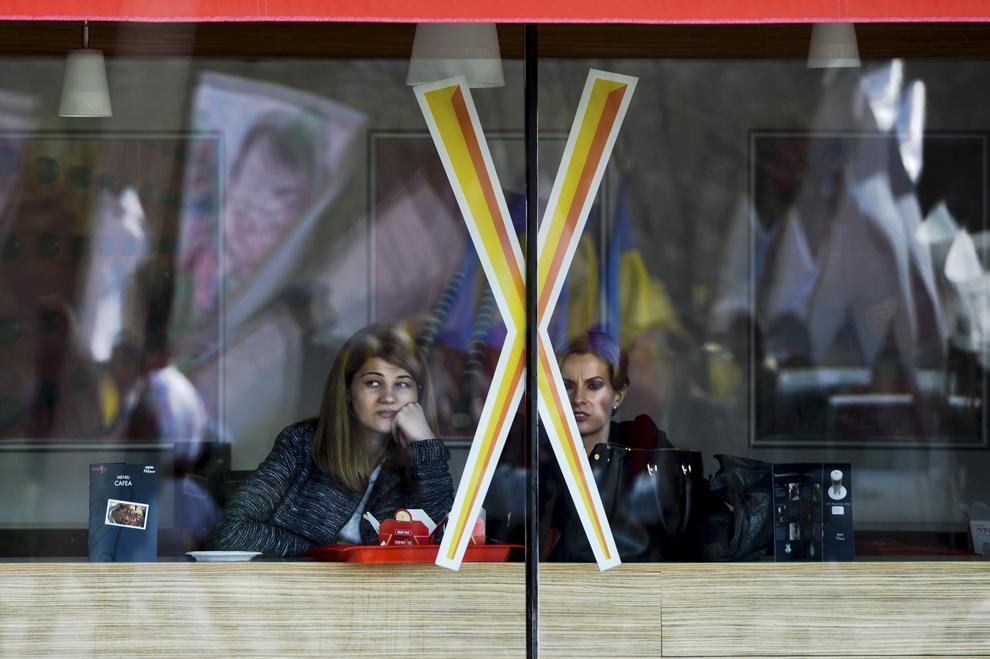 """Două tinere urmăresc, din interiorul unui restaurant, mitingul de protest """"Salvaţi pădurile României"""" organizat de Federaţia Proprietarilor de Păduri şi Păşuni din România a """"Nostra Silva"""" în Bucureşti, sâmbătă, 29 martie 2014."""