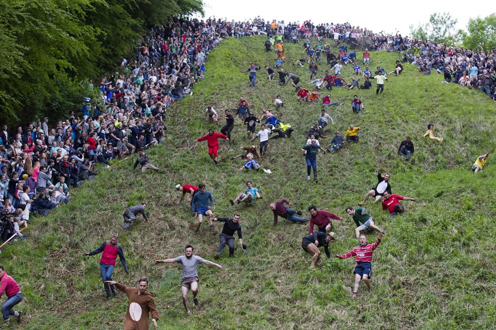 Concurenţi se rostogolesc pe Coopers Hill în urmărirea unei roţi de brânză Double Gloucester, în timpul unui eveniment annual ce se desfăşoară lângă satul Brockworth din apropiere de Gloucester, vestul Angliei, luni, 26 mai 2014.