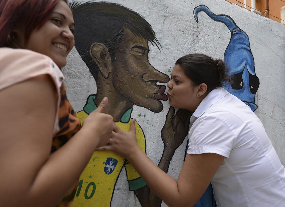 """Două fane sărută un graffiti ce-l întruchipează pe fotbalistul brazilian Neymar sărutând fantoma """"Maracanazo"""" (înfrângerea Braziliei de catre echipa din Uruguay în Cupa Mondiala din 1986), într-o suburbie din Rio de Janeiro, Brazilia, vineri, 9 mai 2014."""