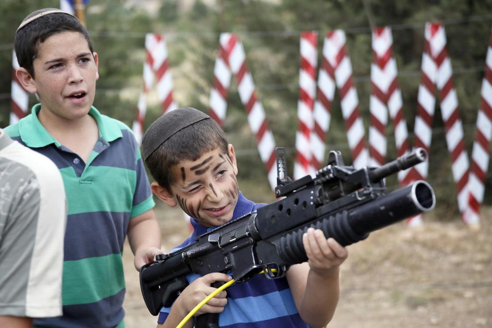 Un copil israelian se joacă cu o armă automată M-16 în timpul unei manifestări ce marchează 66 de ani de independenţă a Israelului,marţi,  6 mai 2014.