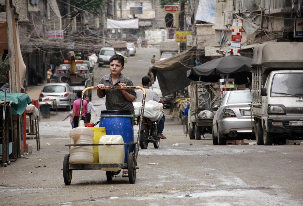 Un copil sirian împinge un cărucior încărcat cu canistre umplute cu apă, în Alep, Siria, joi, 8 mai 2014.