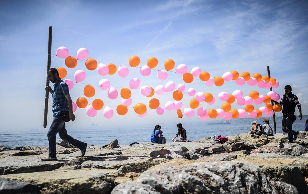 Doi bărbaţi transportă baloane colorate, pe malul marii, în Kadikoy, Istanbul, Turcia, sâmbătă, 3 mai 2014.