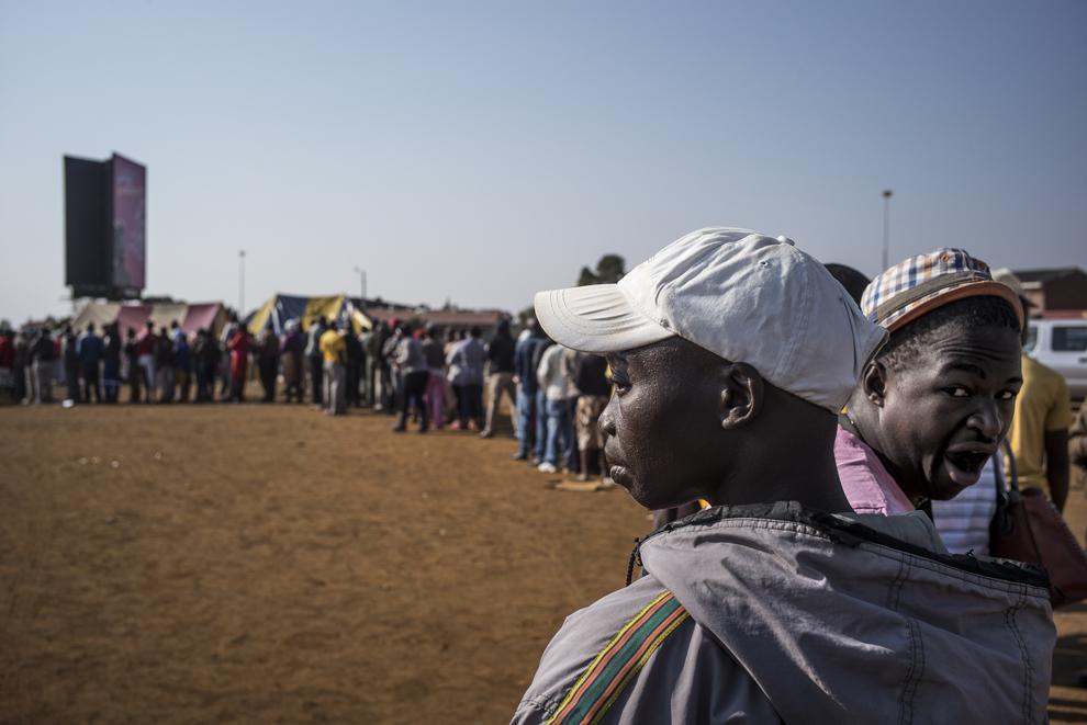 Un alegător din Africa de Sud cască în timp ce asteaptă la coadă alături de alţi alegători, la o secţie de votare din Bekkersdal, în dimineaţa zilei de miercuri, 7 mai 2014.