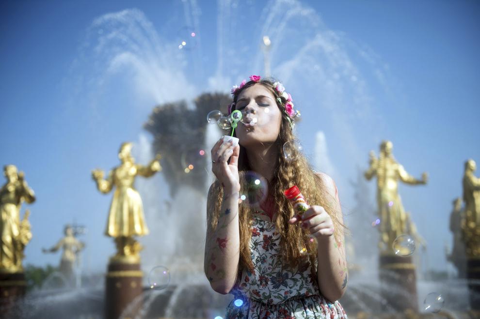 O tânără suflă baloane de sapun, în timpul festivalului Dreamflash, în Moscova, Rusia, duminică, 18 mai 2014.