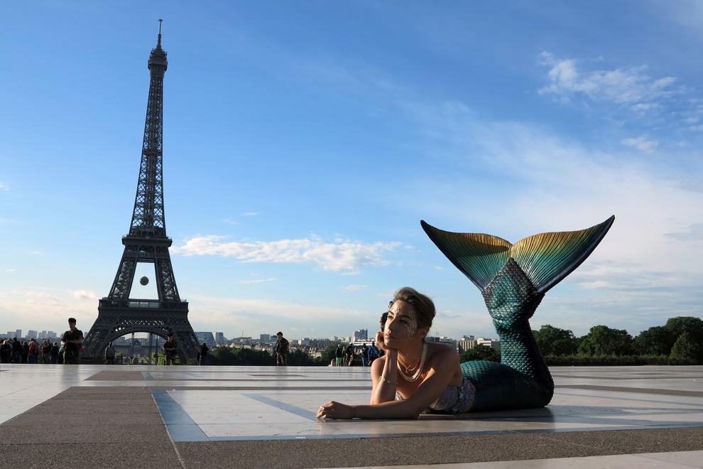 Un model îmbrăcat în sirenă, pozează în faţa turnului Eiffel din Paris, Franţa, joi, 22 mai 2014.