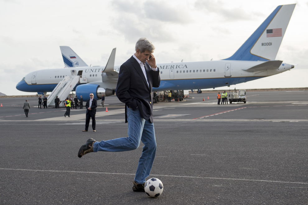 Secretarul de Stat al Statelor Unite ale Americii, John Kerry loveşte o minge de fotbal, în timp ce vorbeşte la telefon aşteptând alimentarea avionului, în Sal Island, Insulele Capului Verde, luni, 5 mai 2014.