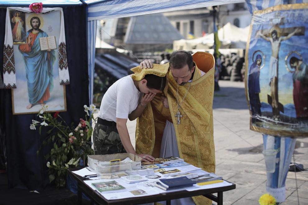 Un preot binecuvântează o femeie ce plânge, într-o capela improvizată în Maidan, Piaţa Independenţei, Kiev, Ucraina, joi, 22 mai 2014.