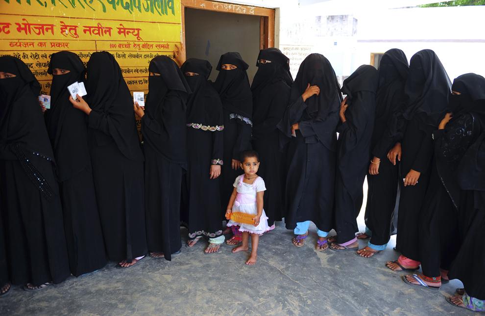 Un copil priveşte femei musulmane ce stau la rând pentru a vota, în Azamgarh, aflat la aproimativ 275 km de Lucknow, în nordul statului Uttar Pradesh, India, luni, 12 mai 2014.