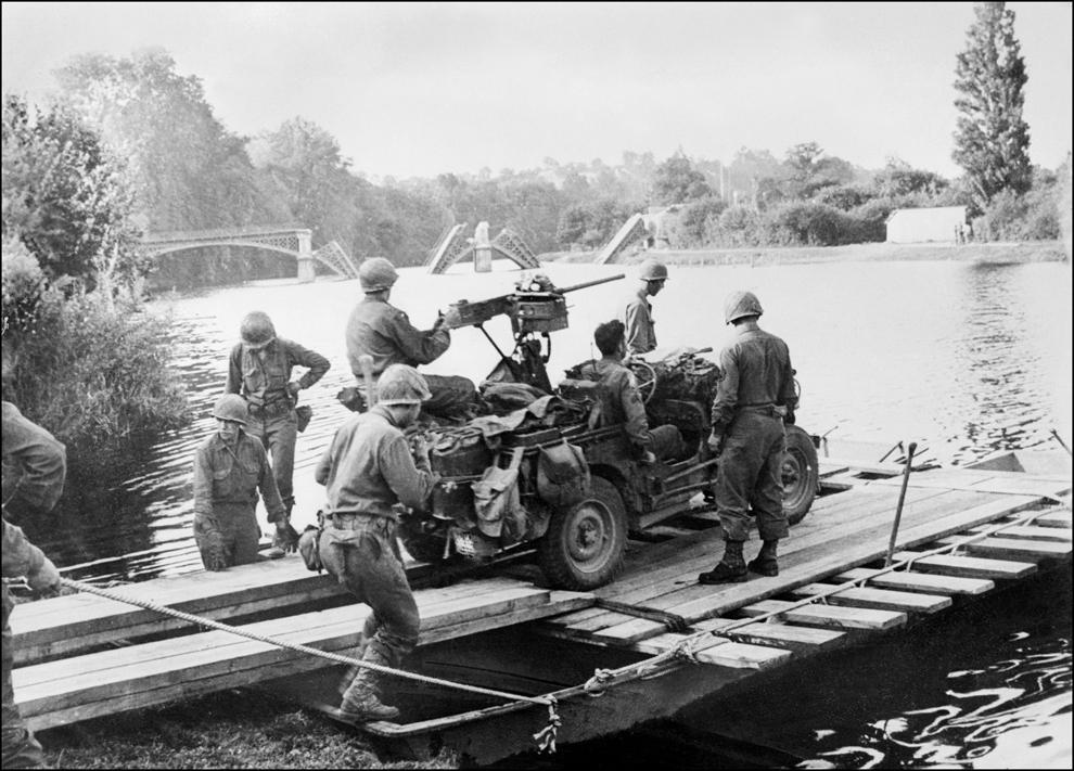 Trupele americane sunt pe cale de a traversa Sena pe lângă un pod distrus de bombardamente, după debarcarea Forţelor Aliate pe plaja din Normandia,în vestul Franţei, în 1944.