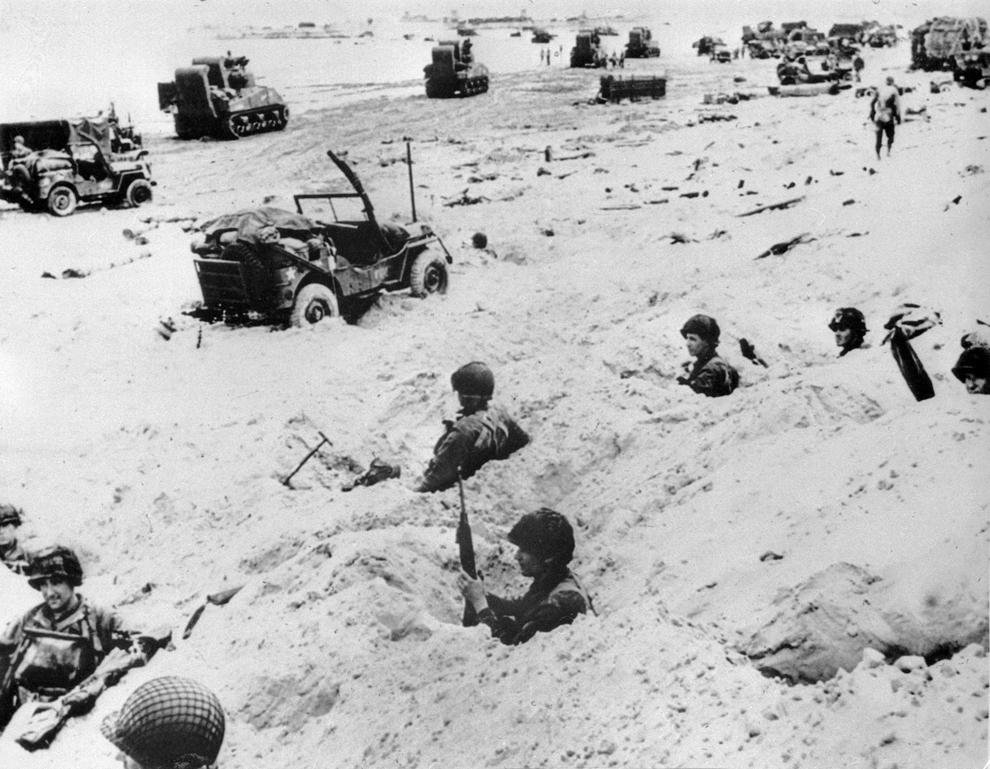 Soldaţi americani stau de pază pe o plajă, marţi, 06 iunie 1944, după ce forţele aliate au luat cu asalt plajele din Normandia în timpul Zilei Z.