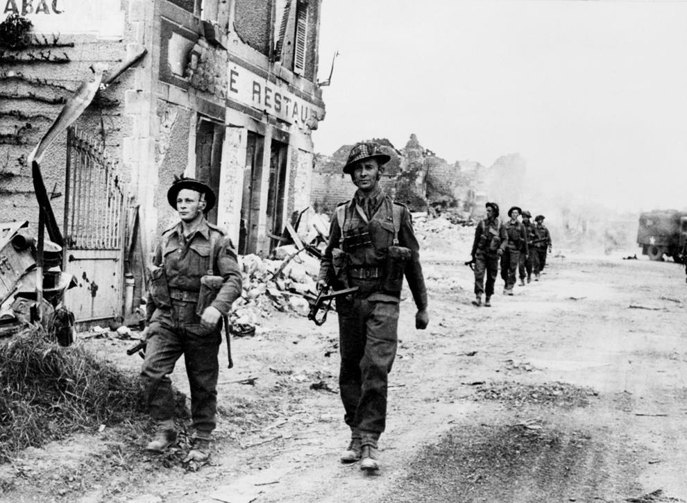 Soldaţi britanici înaintează prin satul Douet, după ce oraşul Bayeux a fost cucerit, joi, 8 iunie 1944, în timpul operaţiunilor Forţelor Aliate din nord-vestul Franţei.
