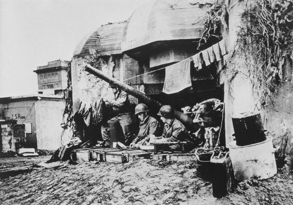 Soldaţi americani îşi usucă hainele, într-un buncăr german din prima linie, în iunie 1944, în timpul operaţiunilor Forţelor Aliate din Franţa.