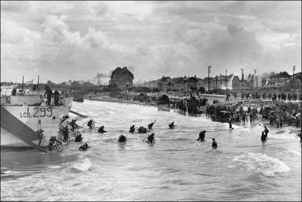 Soldaţi canadieni din brigada a 9-a, debarcă cu bicicletele lor pe plaja Juno, în Bernieres - sur - Mer în timpul operaţiunilor de pe plajele din Normandia, marţi, 6 iunie 1944.