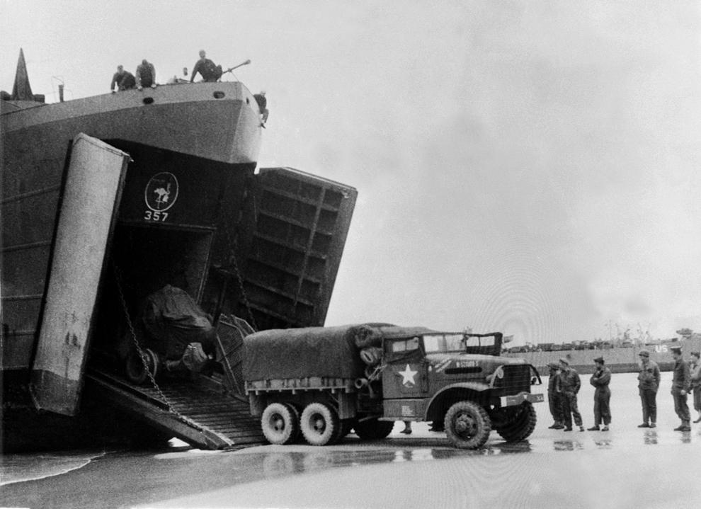 Soldaţi americani debarcă camioane militare pe plaja din Normandia la scurt timp după Ziua Z.