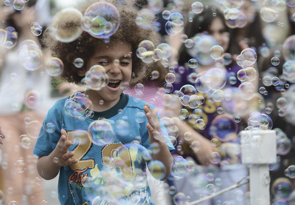 Un băieţel se joacă cu baloane de săpun, în cadrul celei de-a IV-a ediţii a Festivalului internaţional de statui vivante, desfăşurat în Parcul Herăstrău din Bucureşti, sâmbătă, 7 iunie 2014.